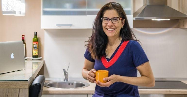 Patricia Figueira do Casal Partiu em uma cozinha de apartamento do Airnbnb. Nômades digitais